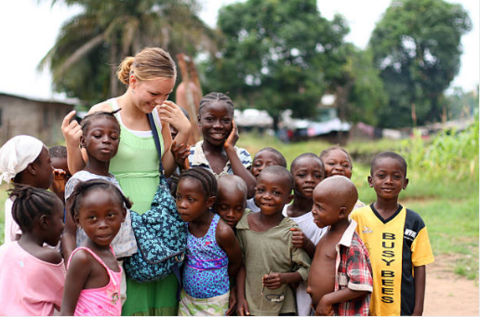 smiling white volunteer/visitor surrounded by group of african children