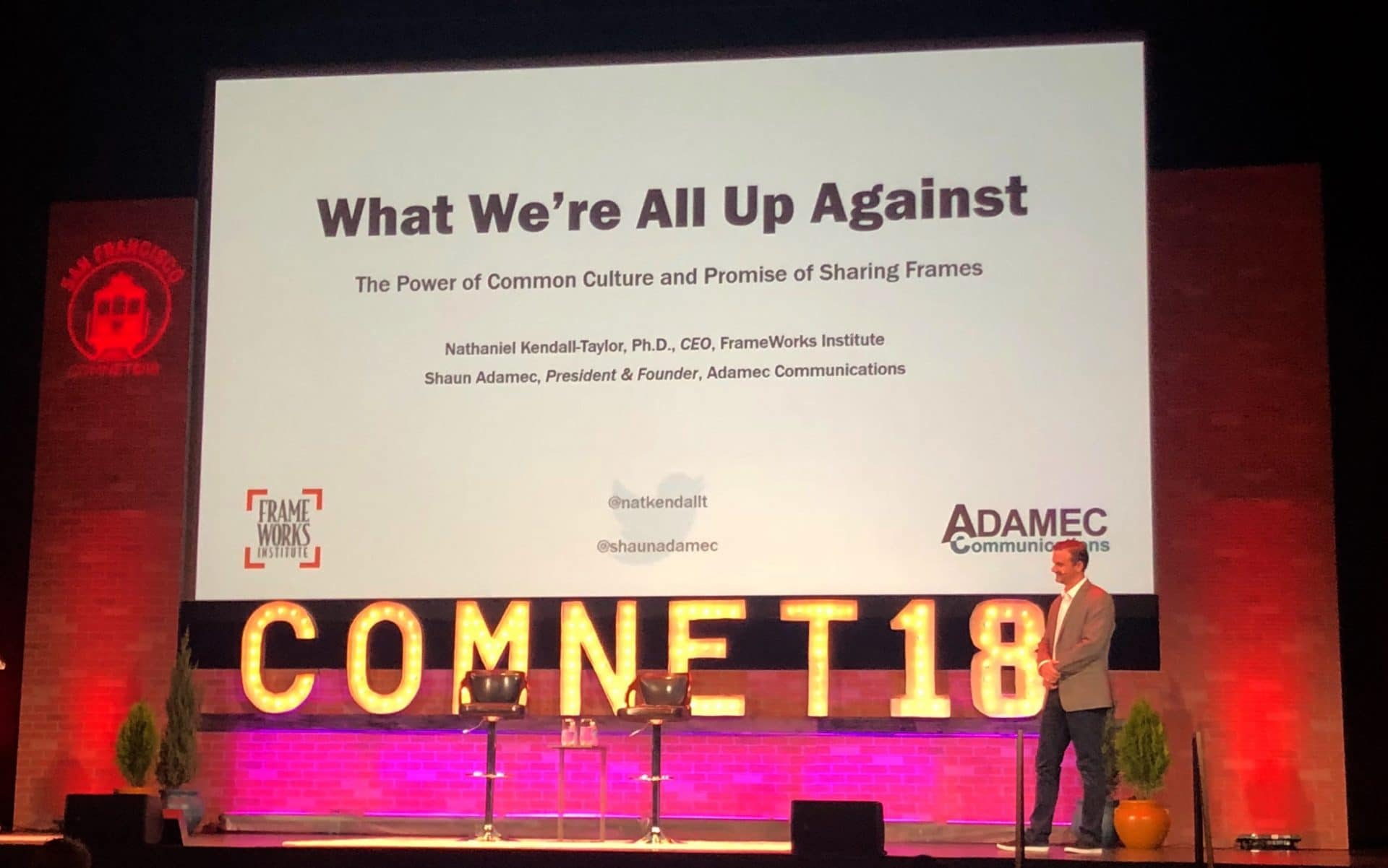 man giving a presentation on theater stage at ComNet18